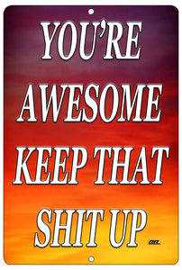 "An image of a purple, red, and yellow funny metal sign from Nuddamakers that says ""You're awesome, keep that shit up"" in white writing."