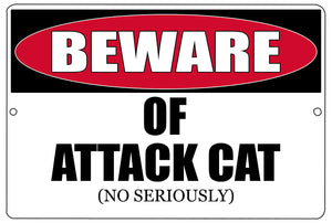 "black, white, and red funny metal sign that says ""beware of attack cat. no, seriously."""
