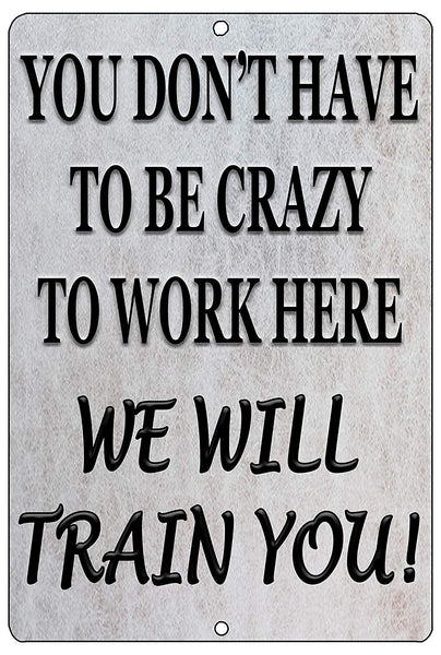 "An image of a gray funny metal sign from Nuddamakers that says ""you don't have to be crazy to work here, we will train you!"" in black writing"