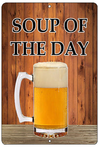 "funny beer sign with wood background and a pint of beer that says ""soup of the day"" in black writing"
