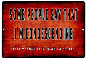 "An image of a red funny metal sign from Nuddamakers that says ""Some people say that I'm condescending (that means I talk down to people)"" in black and white writing."