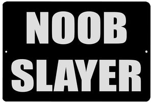 "An image of a black funny metal sign from Nuddamakers that says ""Noob Slayer"" in white writing"