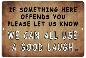 "An image of a brown funny metal sign that says ""If something here offends you, please let us know. We can all use a good laugh"" in black and white writing from Nuddamakers."