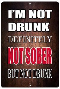 "brown funny drinking sign with white and red writing that says ""I'm not drunk. Definitely not sober, but not drunk."""