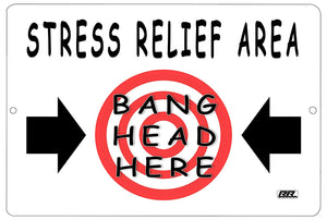 "An image of a white funny metal sign with a red target in the middle that says ""stress relief area: bang head here"" in black writing with two black arrows pointing to the target."