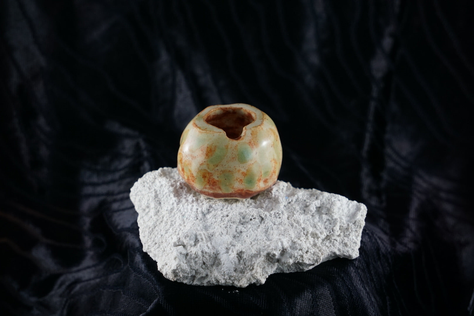 Small, handmade, orange/brown and green ceramic ashtray molded around a piece of white rock.