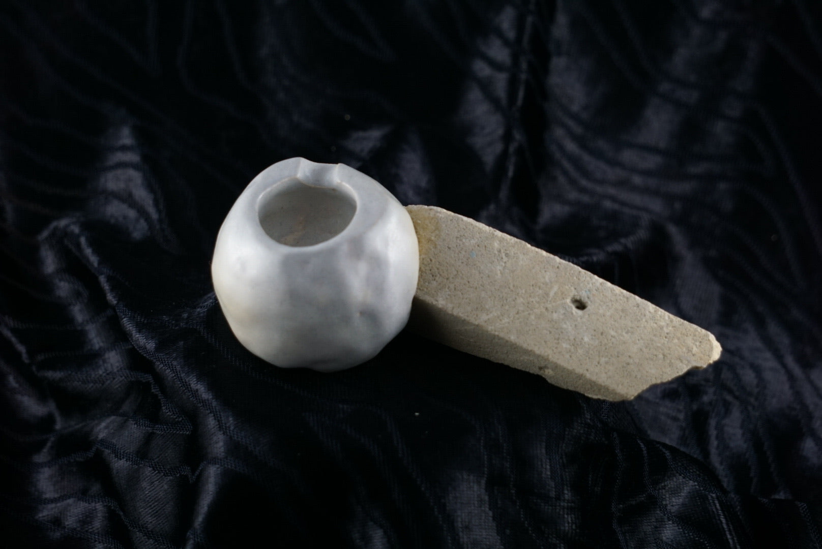 Small, handmade, grey ceramic ashtray molded around a piece of yellow brick