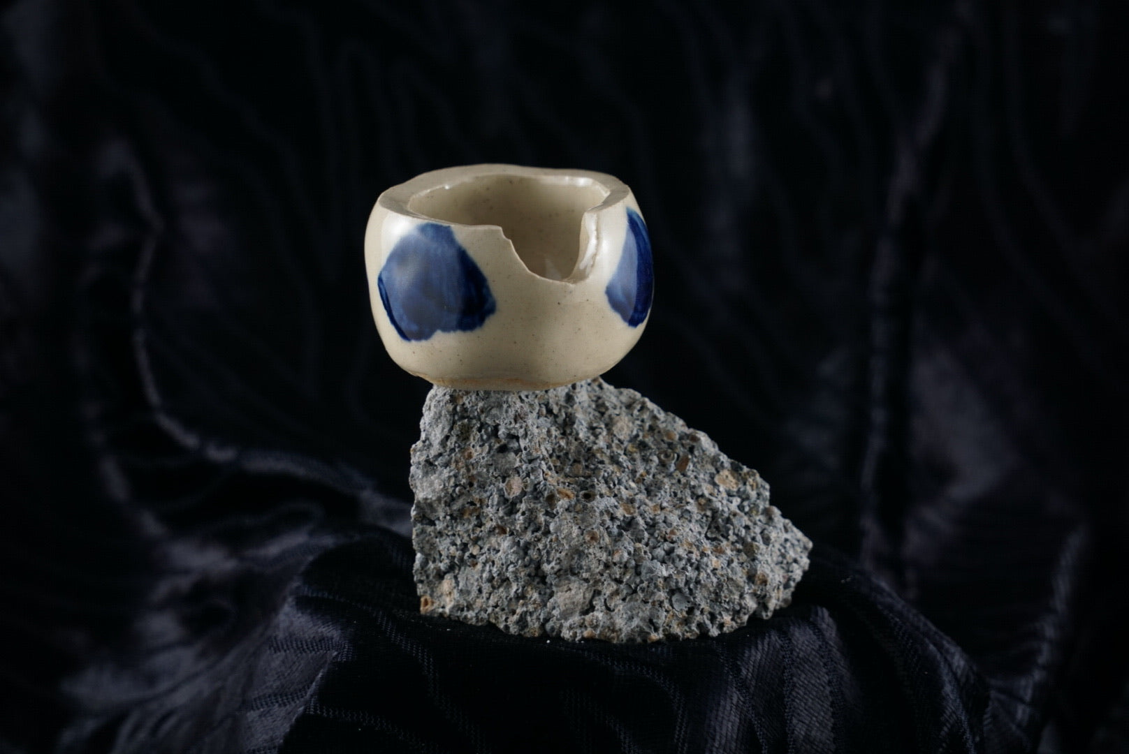 Small, handmade, white and blue ceramic ashtray molded around a piece of black rock