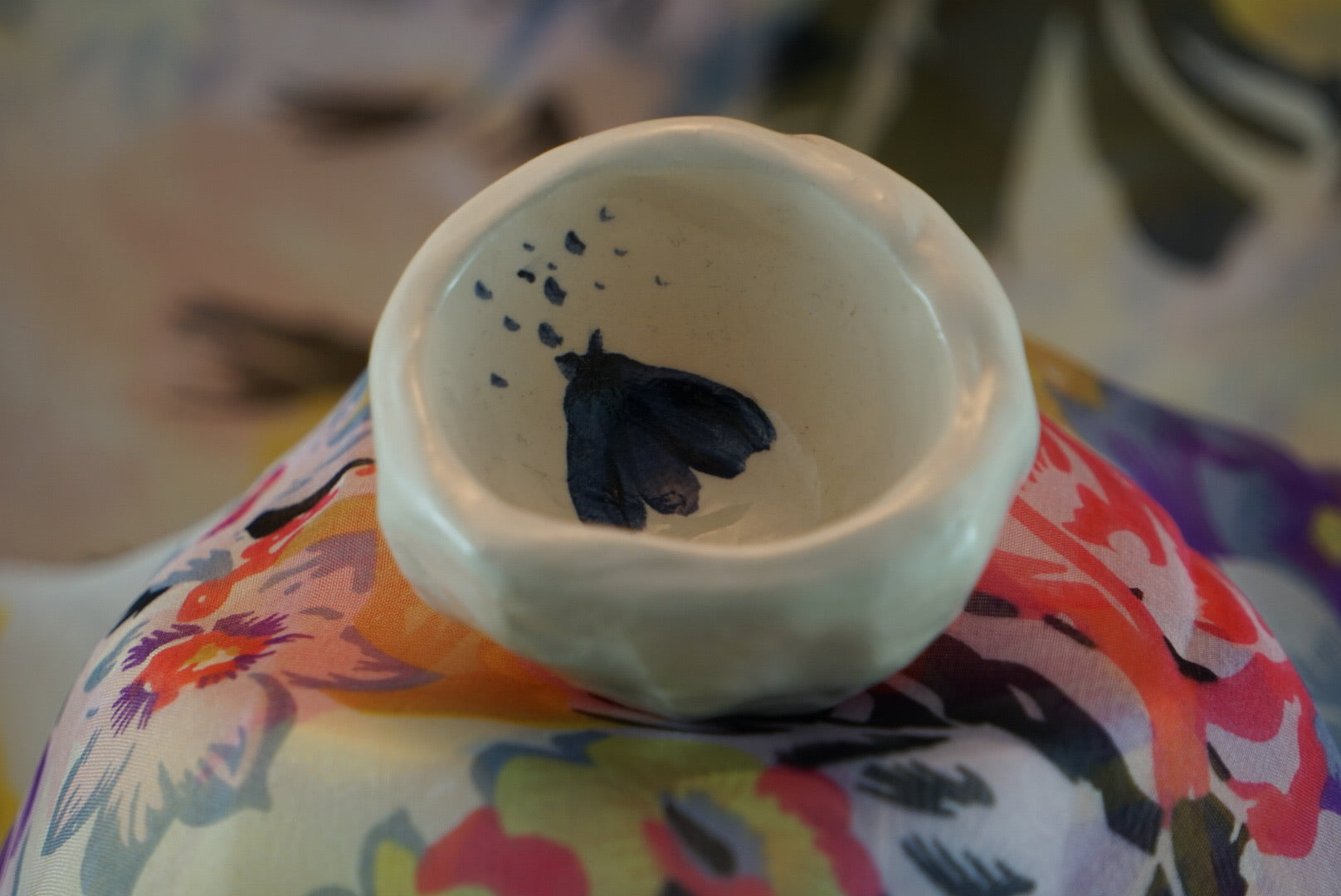 Small, handmade white ceramic pinch pot with loosely drawn blue insects.
