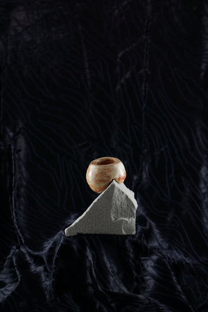 Small, handmade, orange/brown ceramic ashtray molded around a piece of grey rock..