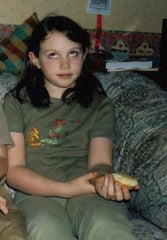 Eilidh as a child wearing a green t shirt and trousers.  They are rolling their eyes.