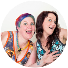 Kirsty and Ros looking happy in a circle. Kirsty has colourful short hair and is on the left. Ros has brown long hair and is on the right. Both women are wearing colourful Molke bras and are doing jazz hands.