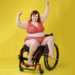 Model is sitting jauntily in a wheelchair with her hands in the air. She's wearing a berries and cherries print underwear set which is mostly red.