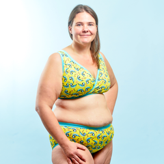 Model is wearing a blue tits print underwear set which is mostly yellow with illustrated blue tits.