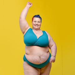 Model is dancing to camera with one arm in the air. She is wearing the Teal set and smiling in front of a yellow background.