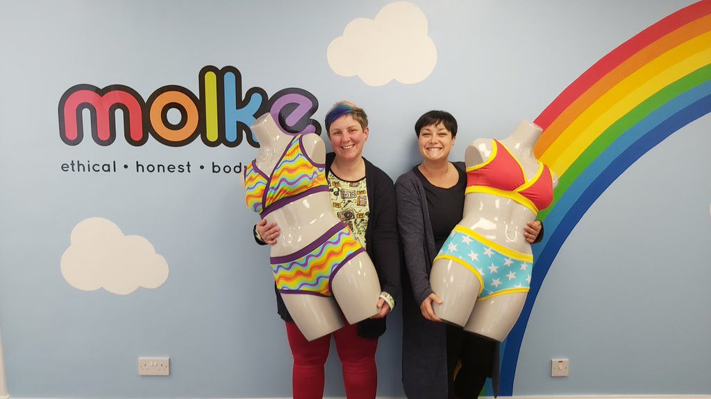 Kirsty and Annie smiling and standing in front of the Molke logo wall while holding up mannequins wearing Molke underwear.