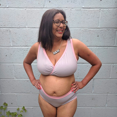 Model is standing outside in front of a concrete wall. She is wearing a grey and pink underwear set.