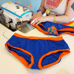 The hands of a machinist at their machine, sewing the leg of a pair of blue and orange pants with a knit gusset. A completed pair is laid out in front of them.