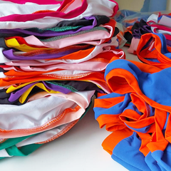 Two piles of briefs made in training. On the left the main colour is white and the briefs have lots of different colour trims. On the right the smaller pile is mainly blue with orange trim.