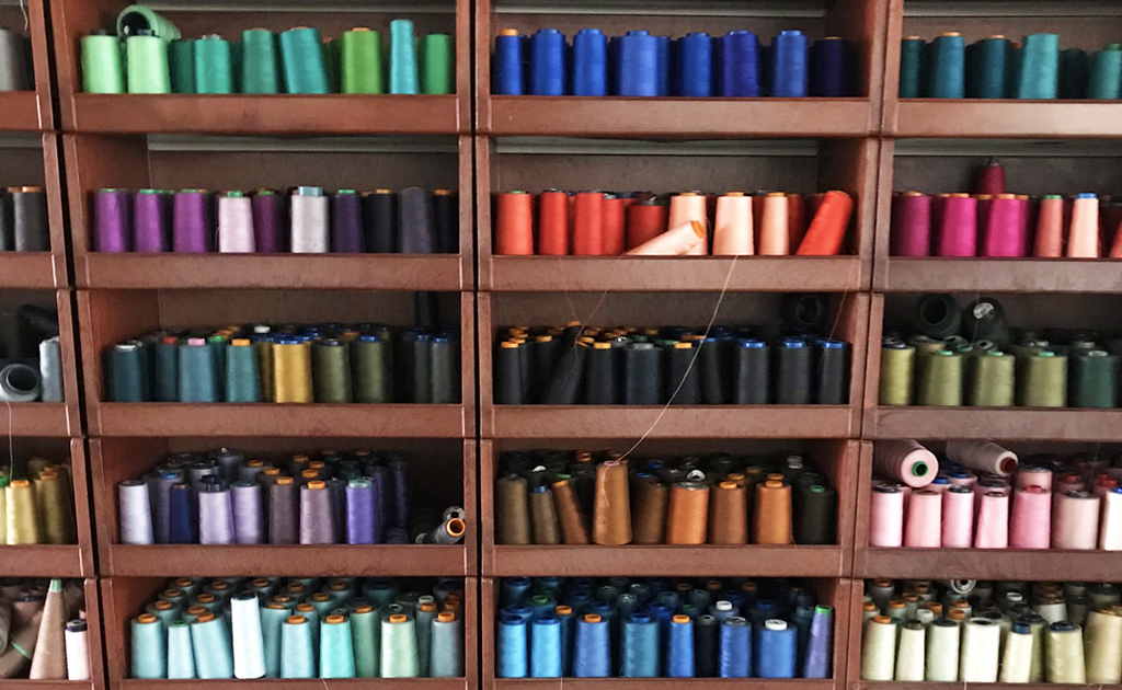 Brown shelves full of different coloured bobbins of thread.