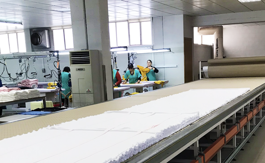 A textiles factory with people working in the background.