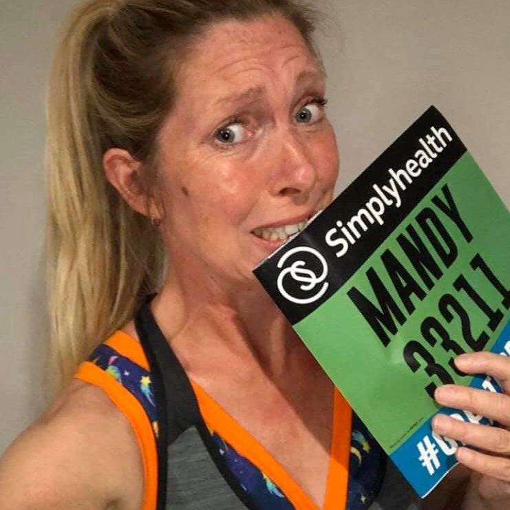 Mandy wearing her running gear and Molke Space bra looking apprehensive and holding her running label.