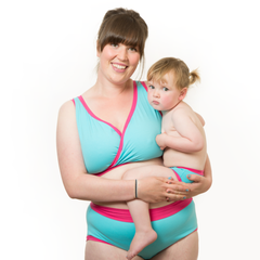 Model is wearing a blue and pink underwear set and holding a small child who is wearing matching children's pants.
