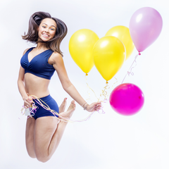 Model is jumping in the air holding balloons and wearing a navy underwear set.