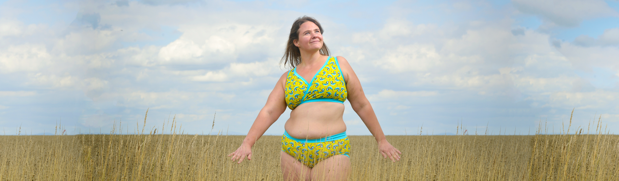 A woman stands in a field of wheat with her arms out and the sky is blue. She looks content. She is wearing a set of Molke underwear in the Blue Tits fabric. It is yellow with illustrated birds on it an a light blue trim.