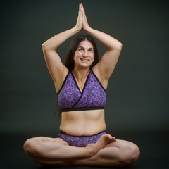 Model is sitting down in a yoga pose with her palms together abover her head. She is wearing a purple lace print underwear set