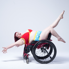 Model is sitting in a wheelchair backwards leaning back with legs and arms outstretched. She is wearing a Power underwear set which is a red bra and blue pants with stars on them.