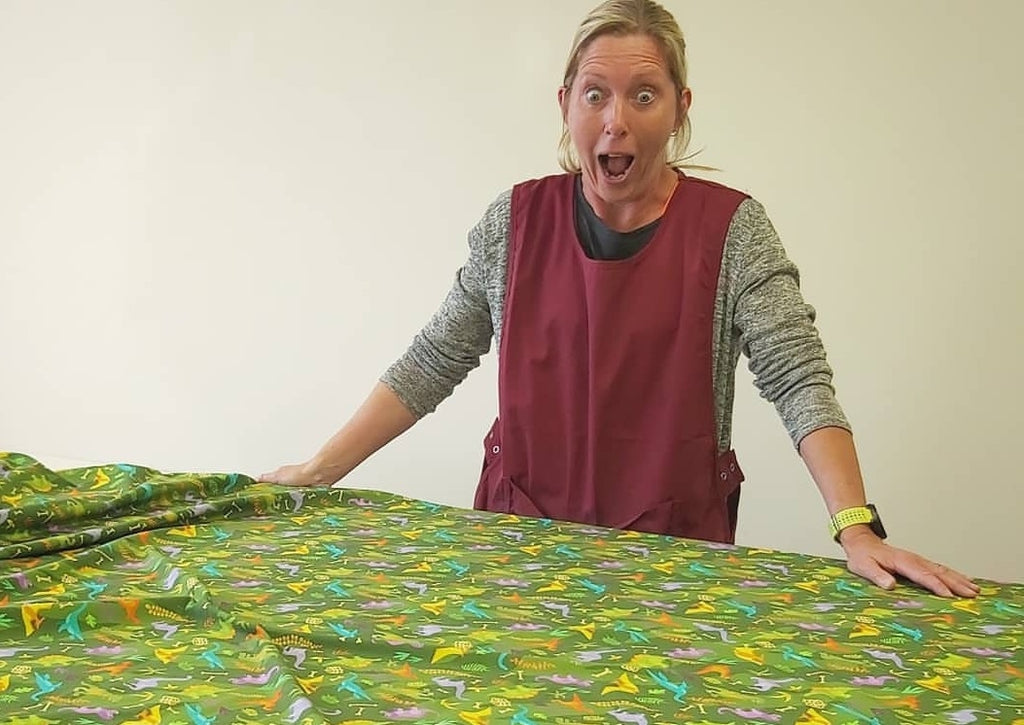 MAndy looking shocked at an unrolled swatch of Dinos fabric covering the pattern cutting table.