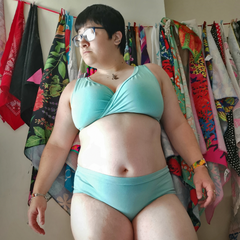 Model stands in her own home wearing the Skye underwear set. It is a light minty blue.