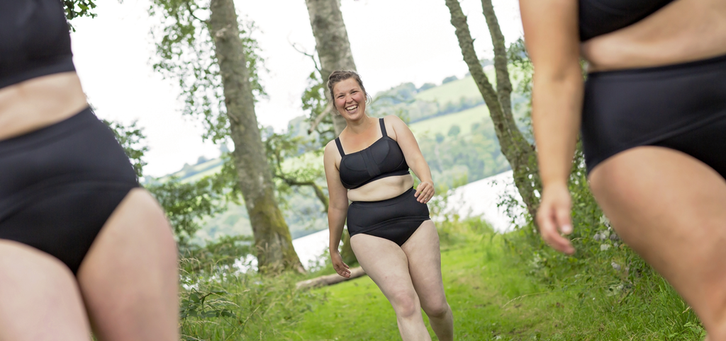 Three models are wearing the Black Molke Swim sets and walking towards you in the woods with the loch behind them through the trees. The two on the left and right are really close to the camera and out of focus you can only see their torsos and tops of legs. The model in the middle is further back and in focus She is smiling widely.