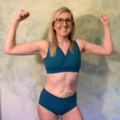 Model is doing a strength pose with her arms. She is wearing a Teal underwear set.