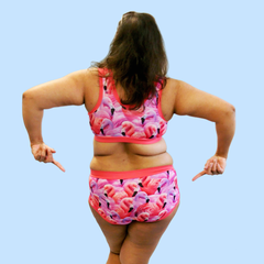 Model is standing with her back to camera and pointing at her bum. She is wearing a flamingo print underwear set.