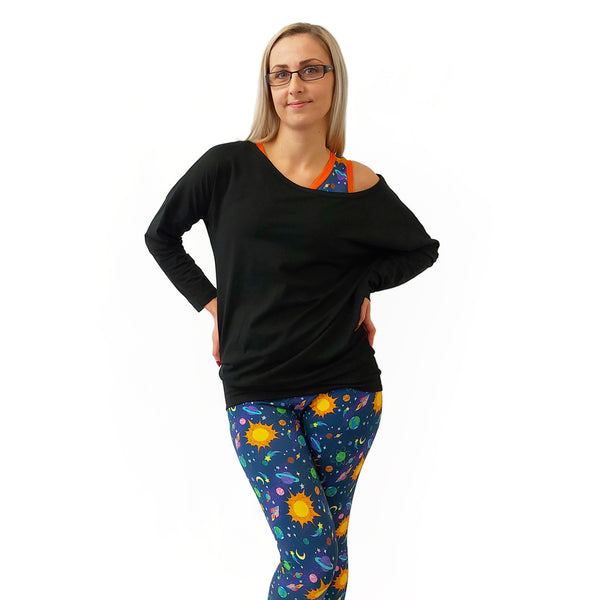 Steph is wearing space leggings and bra with a black long sleeved flash top.  She is smiling to camera with her hands on her hips.  She is against a white background