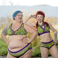 Two models wearing Dinos underwear sets. They have colourful hair and tattoos and are smiling widely.