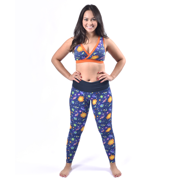 Rebecca is standing with her legs slightly apart and hands on hips. She is smiling and wearing the space leggings with the waist band folded down and the space bra.