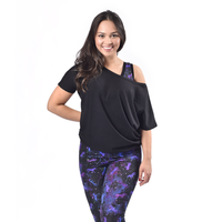 Rebecca facing camera with on arm behind her back wearing Universe leggings and bra with black flash top. The top is tucked into the waist band of her leggings to make it a little shorter.