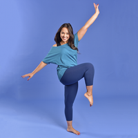 Rebecca is modelling the navy leggings and teal flash top. She is kicking one knee in the air with one arm up and one down against a sky blue background.