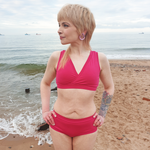 Model wearing a Raspberry set on the beach. You can see the small ships on the sea behind her in the horizon.