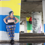 Claire is leaning against a concrete pillar under a bridge surrounded by colourful graffiti. She is wearing Space bra and leggings and is looking off to the right of the image.