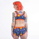 Model stands with her back to camera wearing the Space set with orange trim. She has orange hair and tattoos.