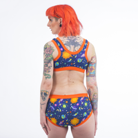 Model with her back to camera wearing the Space set with orange trim. She has orange hair and tattoos.