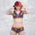 Model wearing the Space underwear set with orange trim. She is pushing her purple and orange hair behind her ears. She has glittery makeup and tattoos.