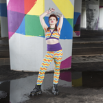 Model is standing in front of a concrete pillar wearing wavy rainbow leggings and bra. She is holding her hands above her hear and has large boots on.