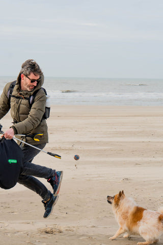 Daan cleaning up the beach and plogging with his dog