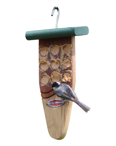 chickadee eating peanut butter on cedar feeder