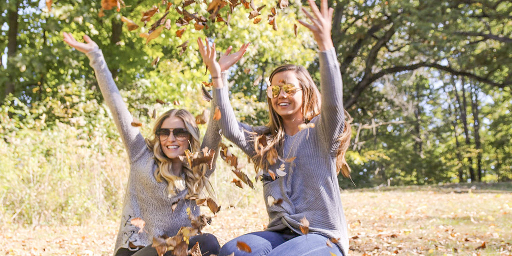 Trendy sweaters for every day style. Girls throwing leaves.